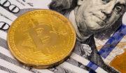 Moeda de Bitcoin em cima de notas de 100 dólares