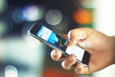 homem olhando o aplicativo do facebook no celular